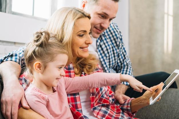 Uśmiechnięty rodzinny dopatrywania wideo podczas gdy córka wskazuje na cyfrowej pastylce