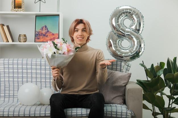 Uśmiechnięty rozkładający rękę przystojny facet na szczęśliwy dzień kobiet trzymający bukiet siedzący na kanapie w salonie