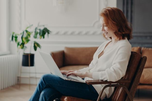 Uśmiechnięty rudowłosy freelancer siedzi w fotelu, klawiatury na laptopie, przesyła niezbędny materiał do opracowania strony, pozuje w nowoczesnym mieszkaniu, podłączonym do bezprzewodowego internetu.