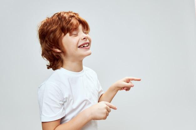 Uśmiechnięty rudy chłopiec przycięte tło gestykuluje rękami szare tło emocje zabawa