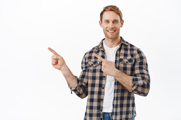 Uśmiechnięty rudy męski model wskazujący palcami w lewo i pokazujący dobrą reklamę, ofertę promocyjną, stojący szczęśliwy i pewny siebie na białej ścianie.