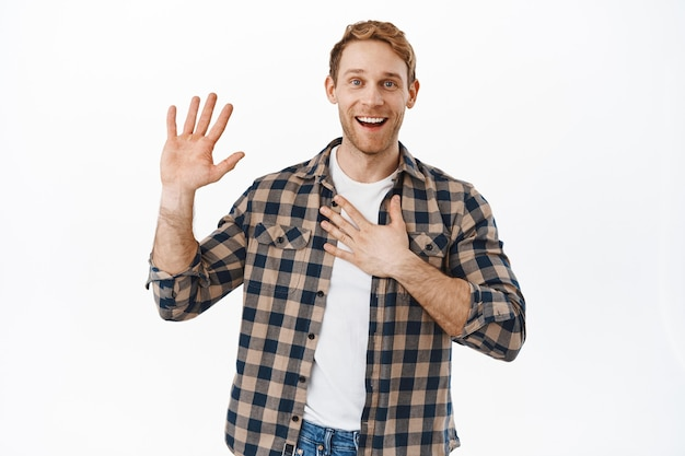 Uśmiechnięty rudy mężczyzna trzymający jedną uniesioną, a drugą rękę na sercu, przedstawia się, moje imię miło cię poznać, witam się, stojąc przyjaźnie i szczęśliwie na białej ścianie