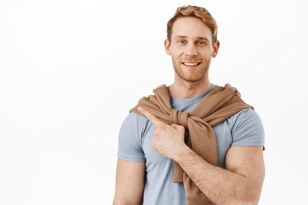 Uśmiechnięty rudy mężczyzna z dużymi mięśniami bicepsów, wskazujący na lewy górny róg, pokazujący reklamę produktu na przestrzeni kopii, stojący nad białą ścianą