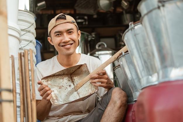 Uśmiechnięty rzemieślnik trzymający śmieci z szufelką, pokazujący do przodu w sklepie ze sprzętem agd