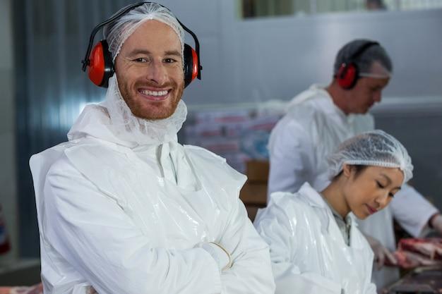 Uśmiechnięty rzeźnik w ochronne słuchawki