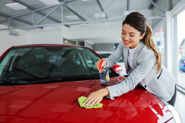 Uśmiechnięty schludny żeński sprzedawca samochodów pocierający samochód detergentem i szmatką