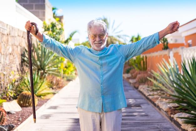 Uśmiechnięty siwowłosy starszy mężczyzna na zewnątrz trzyma laskę spacerową.