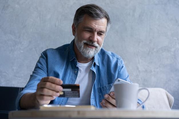 Uśmiechnięty siwy mężczyzna z lat 50-tych płacić rachunki online za pomocą gadżetu nowoczesnego smartfona i karty kredytowej. szczęśliwy dojrzały klient banku dokonać zakupu płatności internetowych na telefon komórkowy z domu. koncepcja technologii.