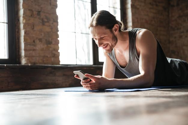 Uśmiechnięty skoncentrowany sportowiec używa telefon komórkowego