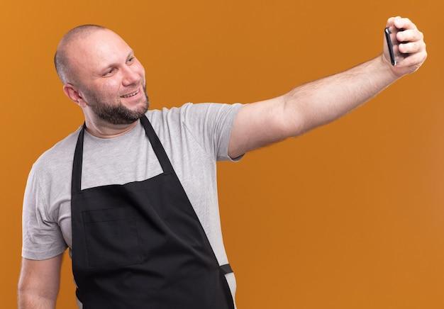 Uśmiechnięty słowiański mężczyzna w średnim wieku fryzjer w mundurze weź selfie na pomarańczowej ścianie