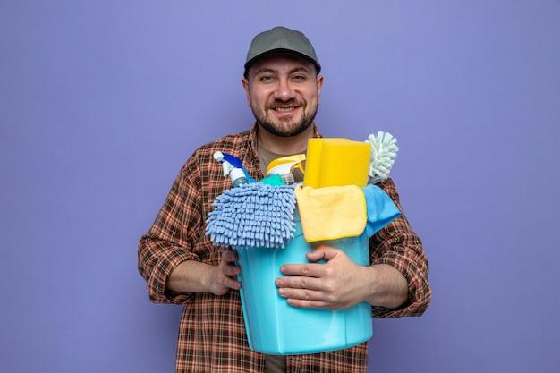 Uśmiechnięty słowiański sprzątacz posiadający sprzęt do czyszczenia