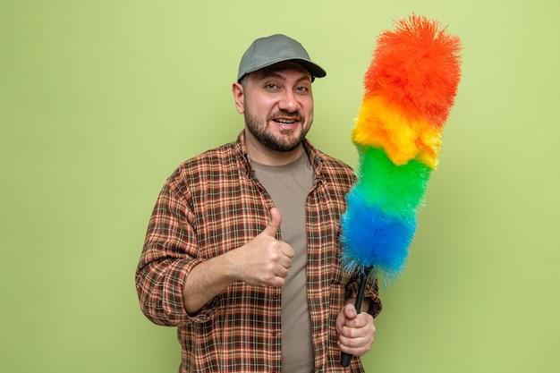 Uśmiechnięty słowiański sprzątacz trzymający miotełkę z piór i trzymający kciuki w górę