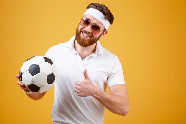 Uśmiechnięty sportowa mienia piłki nożnej piłka i seansu kciuk up
