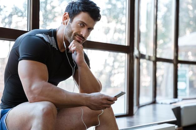 Uśmiechnięty sportowiec ubrany w czarną koszulkę słuchający muzyki