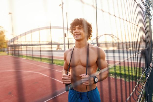 Uśmiechnięty sportowy przystojny mężczyzna z kręconymi włosami stojący na boisku obok ogrodzenia z drutu i skakanka na szyi