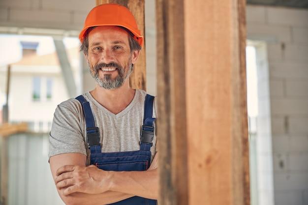 Uśmiechnięty sprawny pracownik budowlany z założonymi rękami uśmiecha się do kamery at