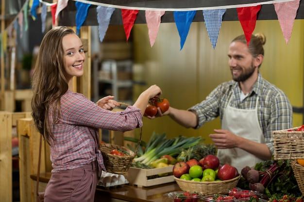Uśmiechnięty sprzedawca, dając pomidory do kobiety przy kasie w sklepie spożywczym