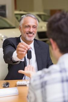 Uśmiechnięty sprzedawca daje klientowi samochodowi klucze