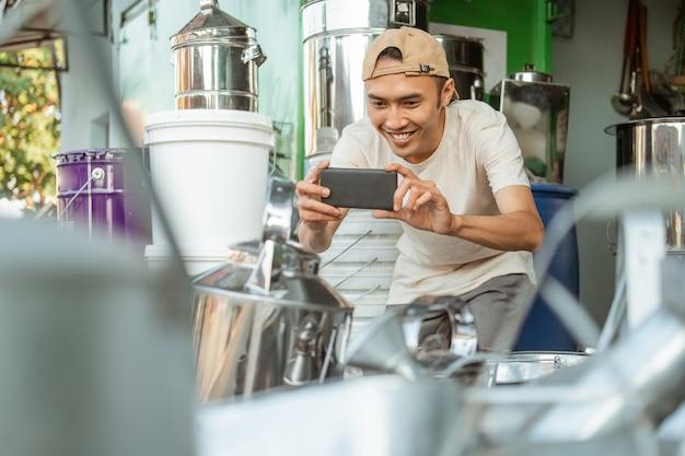 Uśmiechnięty sprzedawca, który używa aparatu w telefonie podczas robienia zdjęć towarów do sklepu internetowego w sklepie agd