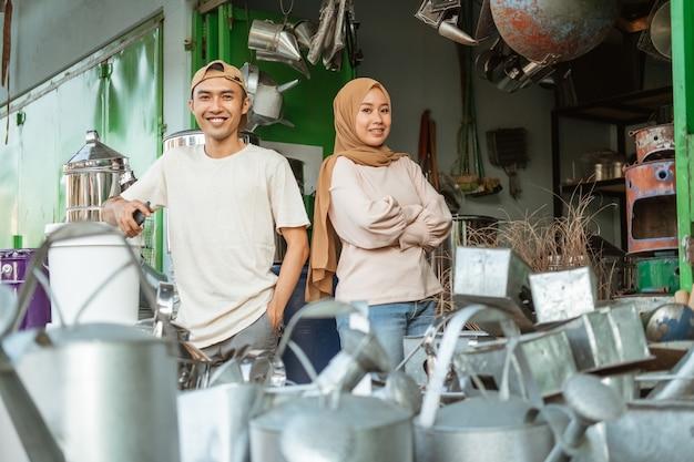 Uśmiechnięty sprzedawca para stojący wśród towarów w sklepie agd