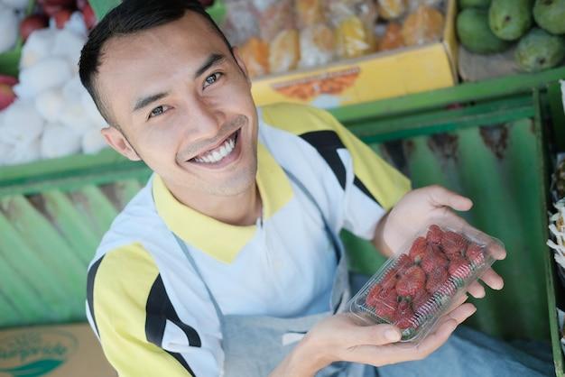 Uśmiechnięty sprzedawca płci męskiej niosący pakiet truskawek w dwóch rękach w sklepie z owocami