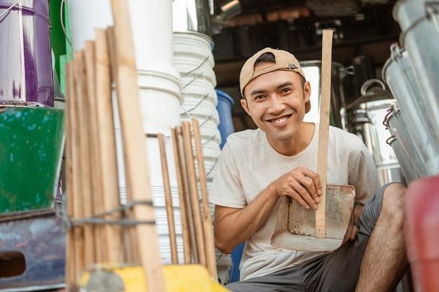 Uśmiechnięty sprzedawca płci męskiej posiadający śmieci z szufelką patrząc na kamery w sklepie agd