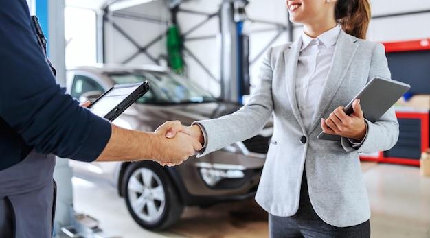 Uśmiechnięty sprzedawca samochodów, ściskając ręce z mechanikiem, stojąc w salonie samochodowym. ważne jest, aby mieć współpracę z obu stron.