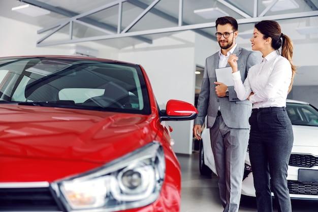 Uśmiechnięty sprzedawca samochodów stojący w salonie samochodowym z klientem i pokazujący samochody na sprzedaż.