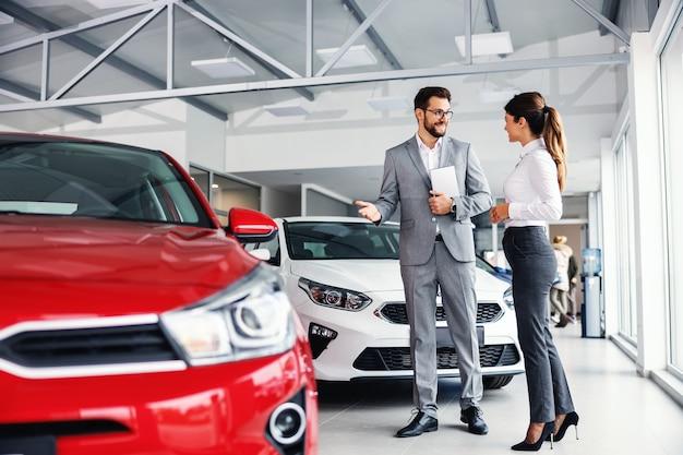 Uśmiechnięty sprzedawca samochodów stojący w salonie samochodowym z klientem i pokazujący samochody w sprzedaży.