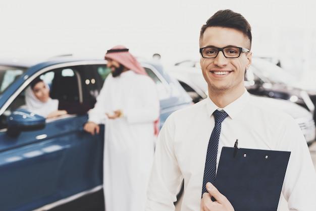Uśmiechnięty sprzedawca samochodów w auto salon vip arab clients.