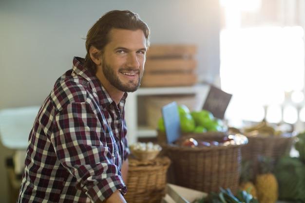 Uśmiechnięty sprzedawca stojący przy ladzie w sklepie spożywczym