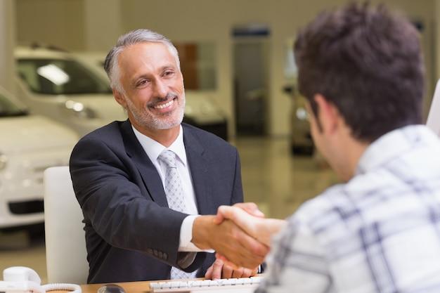 Uśmiechnięty sprzedawca trząść klient rękę