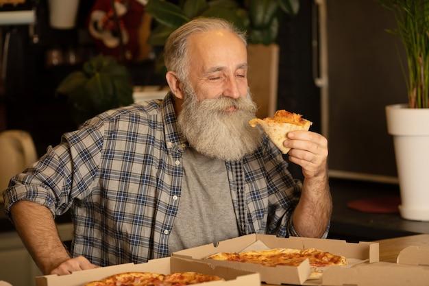 Uśmiechnięty starego człowieka łasowania pizzy plasterka obsiadanie przy żywym pokojem. brodaty starszy mężczyzna je włoskiego jedzenie.