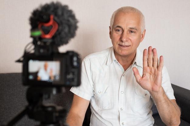 Uśmiechnięty starszy bloger nagrywa nowy vlog, będąc w domu