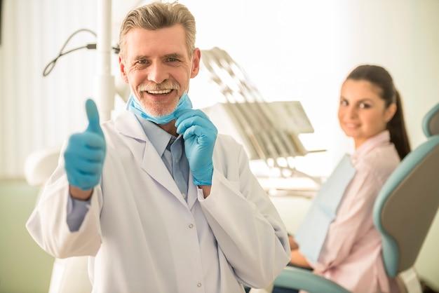 Uśmiechnięty starszy dentysta pokazuje kciuk up.