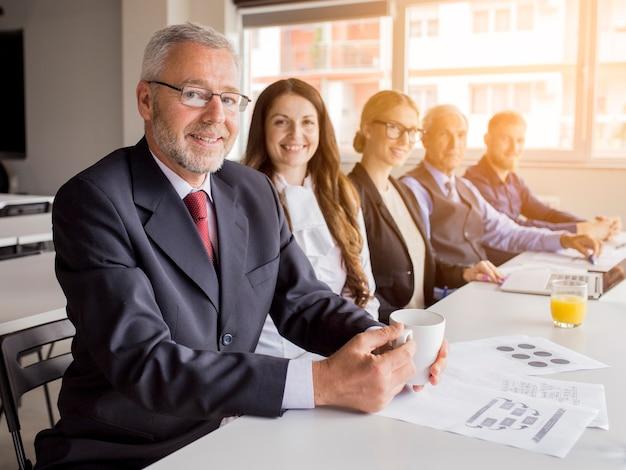 Uśmiechnięty starszy kierownik z jego kolegami siedzi wpólnie w spotkaniu