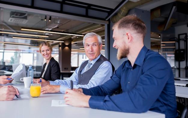Uśmiechnięty starszy kierownik z jego pracownikami siedzi wpólnie w spotkaniu