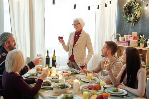 Uśmiechnięty starszy kobieta trzyma kieliszek czerwonego wina podczas opiekania przy stole serwowane przed jej rodziną w święto dziękczynienia