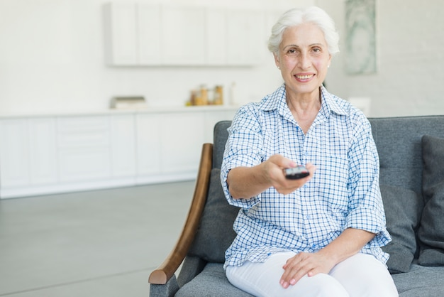 Uśmiechnięty starszy kobiety obsiadanie na kanapie używać pilot do tv w domu