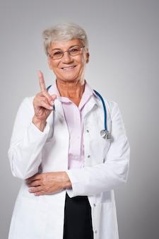 Uśmiechnięty starszy lekarz wskazuje palcem