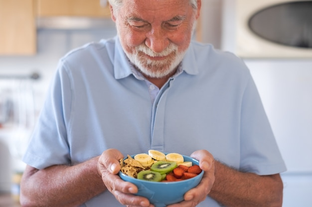 Uśmiechnięty starszy mężczyzna gotowy do spożycia sałatki ze świeżych i suszonych owoców. pora śniadania lub obiadu, zdrowe odżywianie