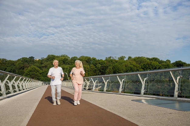 Uśmiechnięty starszy mężczyzna i dama z telefonem komórkowym biegną wzdłuż kładki