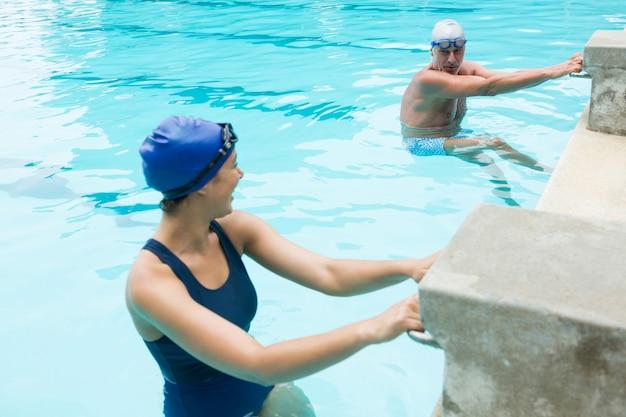 Uśmiechnięty starszy mężczyzna interakcji z kobietą przy basenie