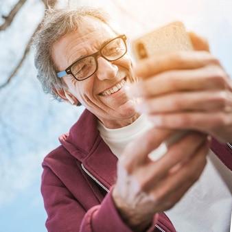 Uśmiechnięty starszy mężczyzna jest ubranym eyeglasses używać mądrze telefon