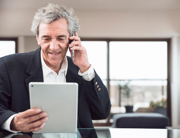 Uśmiechnięty starszy mężczyzna opowiada na telefonie komórkowym patrzeje cyfrową pastylkę przy miejscem pracy