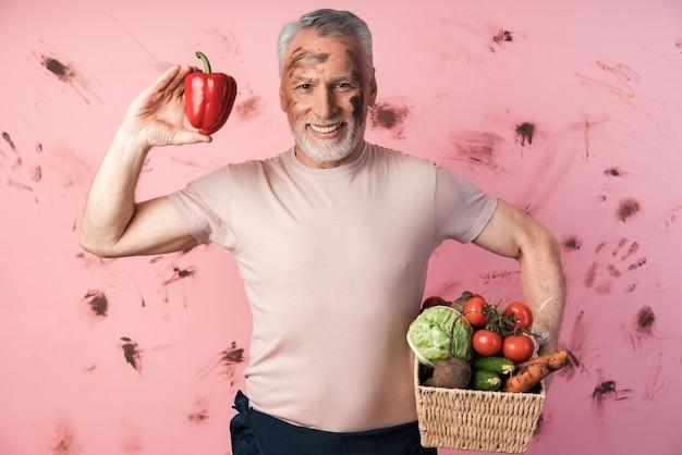 Uśmiechnięty, starszy mężczyzna trzyma kosz warzyw, aw drugiej ręce trzyma czerwoną paprykę