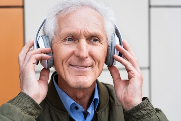Uśmiechnięty starszy mężczyzna w mieście słuchający muzyki na słuchawkach
