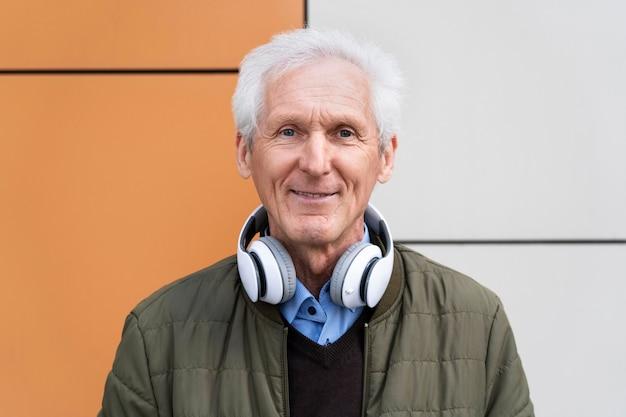 Uśmiechnięty starszy mężczyzna w mieście ze słuchawkami