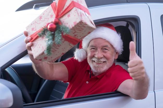 Uśmiechnięty starszy mężczyzna wewnątrz jego samochodu w kapeluszu santa gotowy do dostawy do domu prezentów świątecznych. stary brodaty dziadek robi ok znak ręką