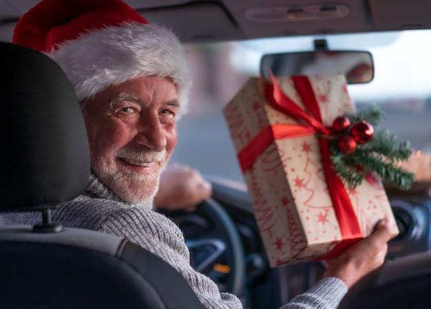 Uśmiechnięty starszy mężczyzna wewnątrz jego samochodu w kapeluszu santa gotowy do dostawy do domu prezentów świątecznych. stary brodaty dziadek z wielkim uśmiechem